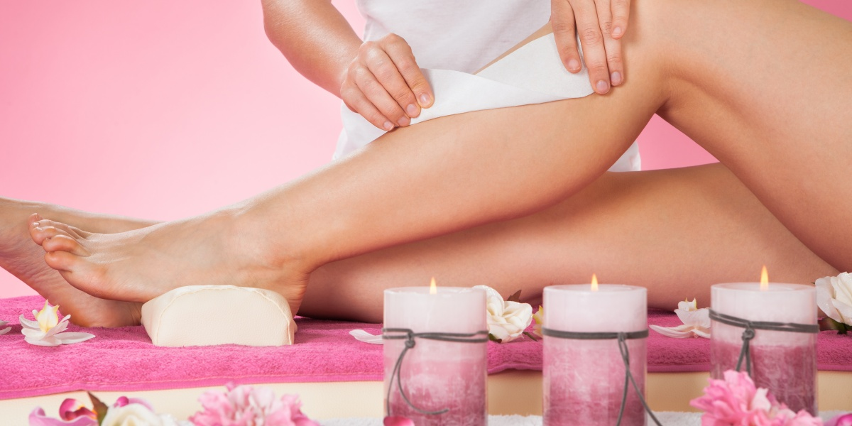 Midsection of female therapist waxing customer's leg at beauty spa